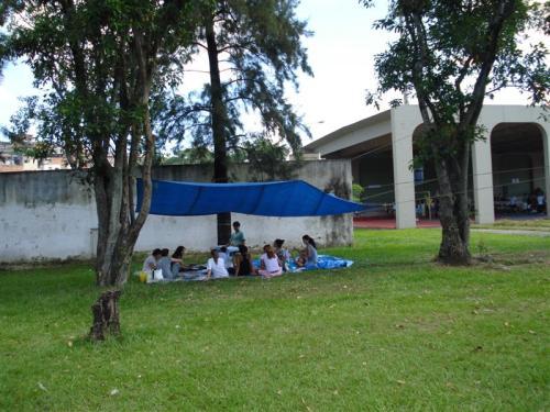 Jovens participam da Oficina de Poesia sentados à sombra das árvores. O ambiente  proporcionou uma produção artística bem inspirada.